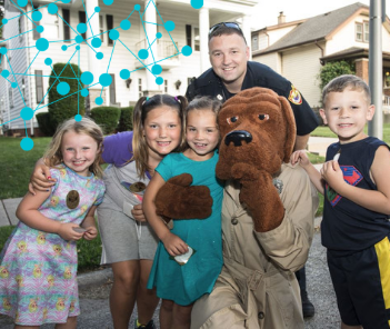 National Night Out photograph of officer with children and McGruff the Crime Dog