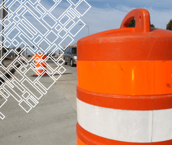 Photograph of orange construction barrel on street under construction
