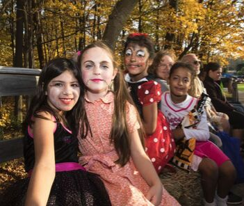 Photograph of smiling girls in costumes at CAAD Halloween in the Park