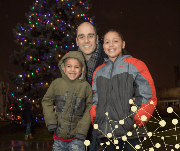 Photograph of Mayor Dan Devine and smiling children in front of West Allis Christmas tree at night