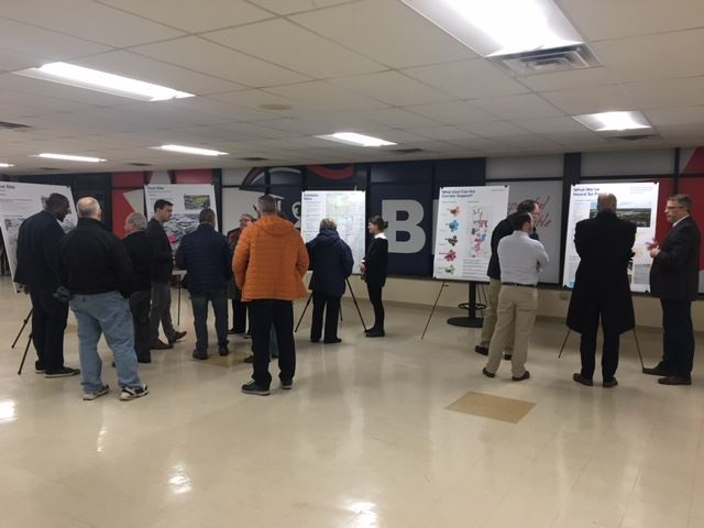 Photograph from back of room at Nov. 13 highway 100 meeting showing groups of people viewing posters